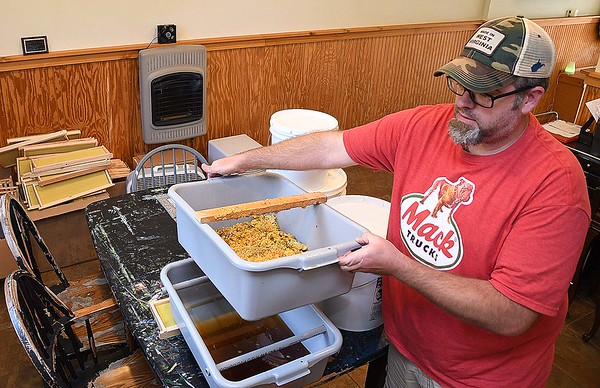 Jason Young, owner, of White Oak Bee Company, processing wax that he produced that will be made into chapstick.<br /> (Rick Barbero/The Register-Herald)