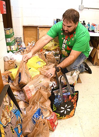Shady Spring High School teacher, Brad Bosticfreshman, sorting through donated food for their Christmas Market that will take place in the Shady Spring High School cafetera, Friday, December, 20 from 3 p.m. to 6 p.m.<br /> (Rick Barbero/The Register-Herald)