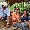 (Brad Davis/The Register-Herald) Thomas Simpson, 2nd from left, and granddaughter Japri Miller, to his right, grin as they notice the camera as they and other Beckley residents hang out in the shade during the annual Juneteenth Community Picnic Saturday afternoon at the Youth Museum. At far left is Greg Claytor and at far right is Beckley NAACP President Barbara Charles. Juneteenth is the oldest known nationwide celebration commemorating the end of slavery in the United States. On June 19th, 1865, Union soldiers led by Major General Gordon Granger landed at Galveston, Texas with news that the Civil War had ended and all slaves were now free, a full two and a half years after President Lincoln's Emancipation Proclamation, which became official January 1, 1863 but had little effect on Texans due to minimal numbers of Union troops stationed in the state. It was after General Lee's surrender in April of 1865 when the U.S. was able to get enough soldiers there to enforce the executive order.