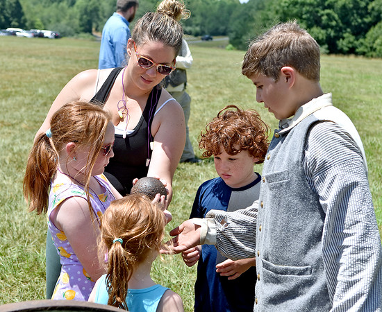 (Brad Davis/The Register-Herald) Attendees get a look at a real cannon ball during Civil War Days Saturday afternoon at Twin Falls Resort State Park.