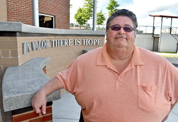 (Brad Davis/The Register-Herald) Former Beckley police officer Tim Berry poses for a quick photo in front of the police memorial at the new station June 21.