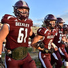 (Brad Davis/The Register-Herald) Woodrow Wilson captains lock arms as they head out to meet the Riverside captains prior to the coin toss Friday night in Beckley.