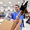 (Brad Davis/The Register-Herald) Young volunteer Tanner Cook smiles as the camera finds him hauling boxloads of gifts for shoppers during the Wyoming County Toy Fund event Sunday morning at Wyoming East High School.
