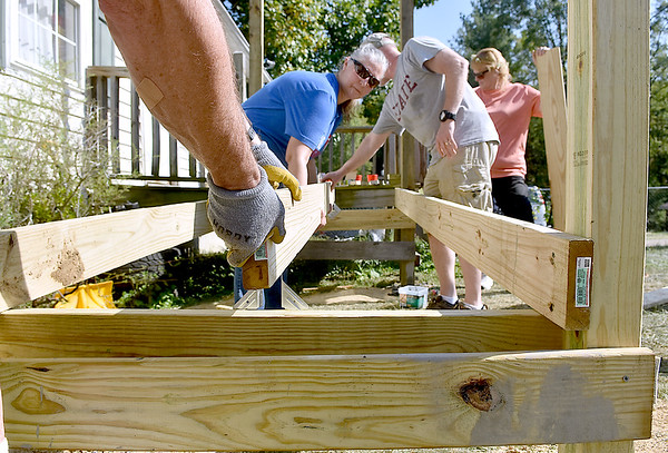 (Brad Davis/The Register-Herald) Parr Claytor (hands), Michell Berkey, middle, and Chuck Noll, put support beams in place as they and fellow volunteers contruct a wheelchair ramp for Harper Heights resident Debbie Green Sunday afternoon. Rev. Susan Claytor looks on at far right.