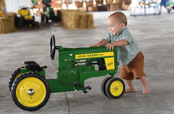 Malachi Gabbert, 1, son of Tyler and Hattie Gabbert, of White Sulphur Springs, pushes a toy John Deere tractor in the Farm for Food Pavillon at the State Fair in Fairlea Friday afternoon.<br /> (Rick Barbero/The Register-Herald)