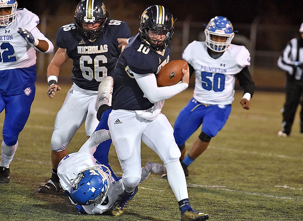 (Brad Davis/The Register-Herald) Nicholas County quarterback keeps the ball to pick up yards on the ground as Princeton defender Ali Abdelwahed (ground) can't bring him down Friday night in Summersville.