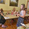 (Brad Davis/The Register-Herald) Charleston resident Ami Smith, left, and other participants take in the strong aroma of a bee's balm herbal extract tea as teacher Victoria Hesterfield, middle, hands out samplers while leading small class through an Herbal Preparations Workshop Saturday afternoon, part of Fayetteville's Wild Weekend Nature Festival. Attendees learned various ways to work with plants to support their health and different methods for extracting the beneficial properties of various types of flora and vegetation, with samples of each tea or balm distributed after each demonstration.