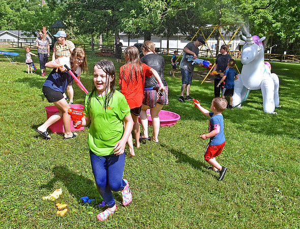 (Brad Davis/The Register-Herald) Participants of all ages duck, dodge and spray the day away with various types of water guns as they take part in a Community Water Battle Sunday afternoon at the Fayette County Park. The free event was organized by the Fayetteville Visitor Center and Generation New River Gorge.