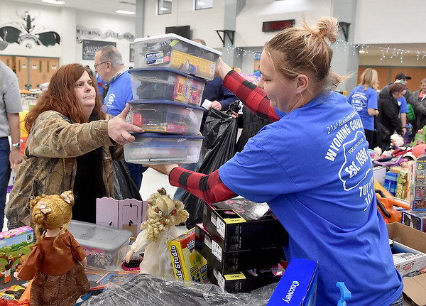 (Brad Davis/The Register-Herald) Volunteer Terri Riggs, right, hands gifts to customers during the Wyoming County Toy Fund event Sunday morning at Wyoming East High School.