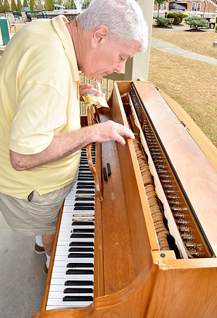 (Brad Davis/The Register-Herald) Mark McGraw inspects the piano placed under the Jim Word Memorial Park gazebo last year to if anything still functions after it was discovered to be battered and rendered useless by vandals over the weekend. Originally gifted to 110 Marshall owner Rebecca Beckett by the late Mike Richmond, the piano was then donated to the City of Beckley. Officials decided to place it under the Word Park gazebo as a way to foster public arts and tap into the growing culture of cities placing instruments in public spaces to encourage street music. City officials said they'll replace the piano through donation.