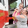 (Brad Davis/The Register-Herald) Mom Brooke Leonhard hoists young daughter Evelynn Zanger out of a Wilderness F.D. (Mt. Lookout area) fire engine after getting the chance to explore its spacious cab during a special Public Safety Day event at Veterans Memorial Park in Summersville Friday afternoon. The event was tied into the final day of the season of Summersville's Popsicles in the Park, which happens every 2nd Friday of the month from May to August and will again next year. Area fire departments were on hand to show off their gear and put on vehicle extraction demos, while area police performed K-9 search demos. Veterans Memorial Park will continue to buzz with activites going forward, with Yoga in the Park every Tuesday year-round from 6:00-7:00 p.m., and a community yard sale set for October 5.