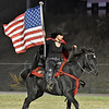 (Brad Davis/The Register-Herald) A young Liberty rider carries the American flag as she gallops across the field on a horse Friday night in Glen Daniel.