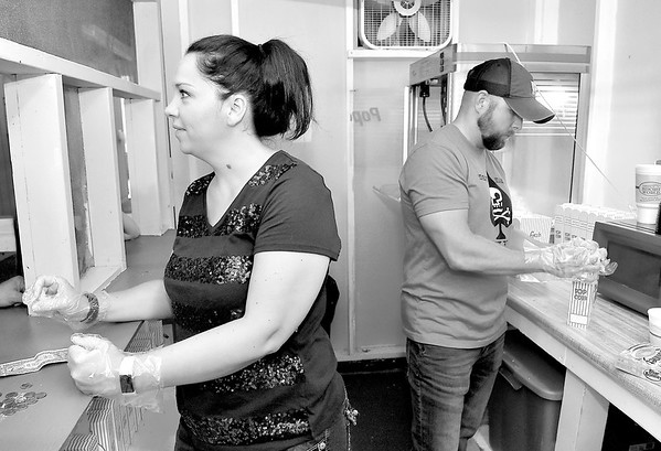 """(Brad Davis/The Register-Herald) Volunteers Samantha and Brandon Gerwig perform the normal and tedious duties of prepping the concession stand at Theatre West Virginia's Cliffside Amphitheatre an hour before another performance of Annie, stocking it with pretzels, popcorn and hotdogs to accomodate the inevitable rush Thursday evening at Grandview Park. The Hico family, also parents to young actress Haven Gerwig who plays one of the two Annies, are known affectionately around the ampitheatre as the """"Hico Psychos"""" and have been at it as devoted helpers all season long. During this year's theatre season, they've all been living camper-style at the campgrounds in Little Beaver State Park to be right next door to Grandview. On top of that, the family has worked hard to get the word out in the community, selling some 300 tickets already during the young season. Friday night was Haven's final performance as Annie, but the family will still be at it for the final two shows (Friday and Saturday) before heading out on a beach vacation, then returning to Little Beaver to get back into the swing as Haven takes on a role in Paradise Park, which runs July 18 through 28."""