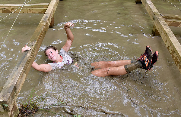 (Brad Davis/The Register-Herald) A participant swims underneath obstacles through muddy water as she and hundreds of other tackle the courses at the Gitty Chix Mud Run Saturday morning at ACE Adventure Resort.