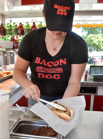 (Brad Davis/The Register-Herald) Bacon Dog employee Darien Tanner spreads bacon on top of a peanut butter-covered hotdog, that's right, peanut butter, Sunday afternoon at the State Fair in Fairlea.