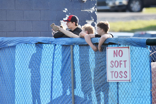 Four youths watch the Class AA Region 3, Section 1 championship game  against Independence and Wyoming Eats on a sand mound in Coal City on Monday. (Chris Jackson/The Register-Herald)