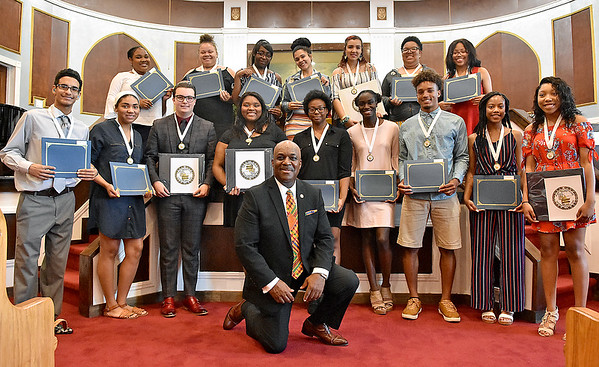 (Brad Davis/The Register-Herald) BEAUTY President Quincy A. Madison proudly takes a knee with this year's honorees as they get together for a group shot at the conclusion of the Graduate Celebration and Awards ceremony Saturday afternoon at Central Baptist Church. Of 19 students recognized at the event, 10 received $1,000 scholarships towards their upcoming college ventures.