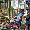 (Brad Davis/The Register-Herald) Danny Green, right, wheels his wife Debbie out onto the front porch of their Harper Heights home to watch a combined crew of volunteers from St. Luke Lutheran Church, St. Stephens Episcopal Church and the Mountain State Centers for Independent Living as they construct a wheelchair accessible ramp for her Sunday afternoon. Debbie has been mostly wheelchair-ridden with some use of a walker, and has had to be helped and/or carried up the stairs onto her porch by accompanying family for the last four years, making simple trips anywhere a huge undertaking. The family, like so many others who live with disabilities, are without adequate handicapped access at their homes with no means or ability to pay for or secure upgrades. Currently, a waiting list for federal funding for such facilities through MSCIL stretches four years and has 113 individuals on it in the state of West Virginia. St. Luke and St. Stephens, through their God's Work, Our Hands program, teamed up with Kelly Elkins at the Mountain State Centers for Independent Living to build a ramp for someone on their waiting list, and hopefully launch a potential longterm project that aims to bring in several other local churches to help provide the access ramps free of charge. It is Elkins' hope that this first project leads to more ramps for people in need who've waited so long, not just just locally but statewide.