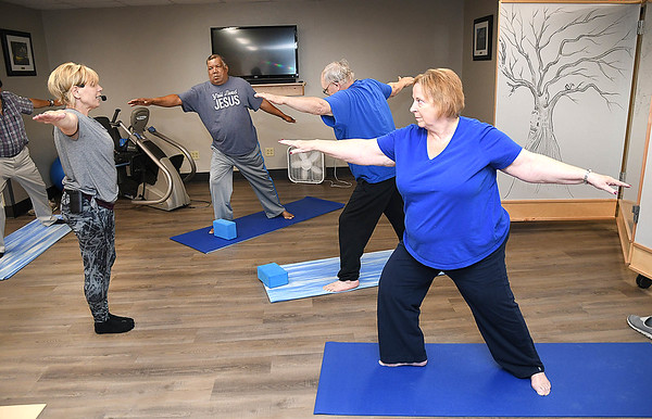 Emilie Mueller, right doing yoga at the Beckley VA Medical Center. Also pictured from left, Jodie Treadway, yoga instructor, Percy Fruit, of Minden and James Wilson of Sophia.<br /> (Rick Barbero/The Register-Herald)