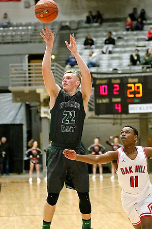 (Brad Davis/The Register-Herald) Wyoming East's McQuade Canada shoots for three as Oak Hill's Jason Manns defends during Big Atlantic Classic action Wednesday night at the Beckley-Raleigh County Convention Center.