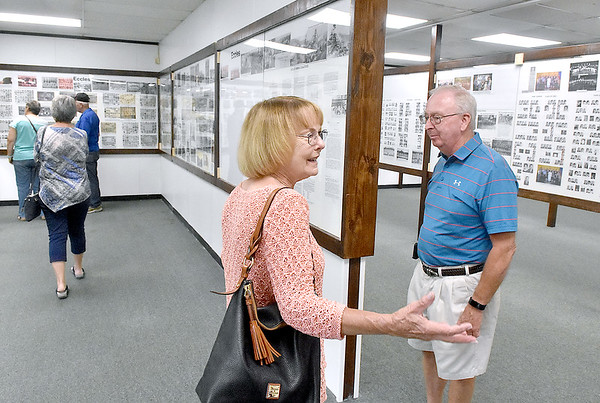 (Brad Davis/The Register-Herald) Lester area natives Sharon Hall, middle, and Randy Trump, right, among other former residents, marvel at the displays packed with photos and history of the once booming region inside the newly opened Trap Hill History Museum Friday afternoon inside the former Lester Elementary School, now Lester's City Hall.