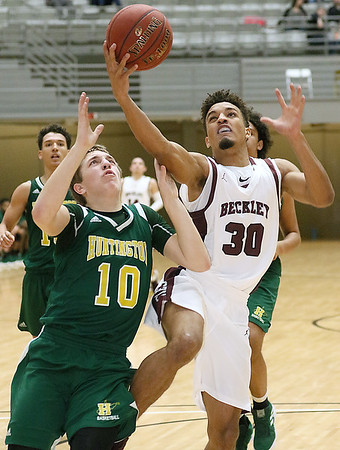 (Brad Davis/The Register-Herald) Woodrow Wilson's Micah Hancock drives to the basket as Huntington's Torin Lochow defends Wednesday night at the Beckley-Raleigh County Convention Center.