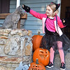 (Brad Davis/The Register-Herald) Kitty cat Audrey Gibson reaches out to pet actual cat Smokey as she and her family set out for Trick or Treating along the Crescent Road neighborhood area Saturday evening in Beckley.