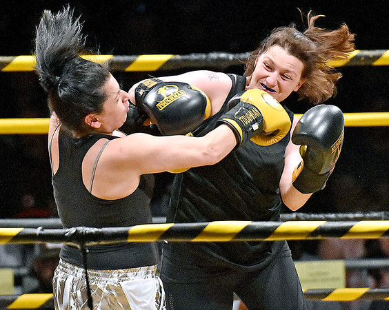 (Brad Davis/The Register-Herald) Mt. Hope's Diane Jackson, right, lands a big right on Glen Daniel's Michelle Lapan during the Original Toughman Contest Friday night at the Beckley-Raleigh County Convention Center. Jackson would win the fight.
