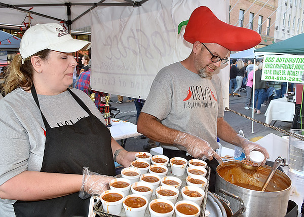 """(Brad Davis/The Register-Herald) Rachel Adkins, left, and Vince """"Pepperhead"""" Conway keep cups of their chili flowing as the Hospice of Southern West Virginia employess prepare trays for the oncoming masses during Chili Night festivities Saturday night in downtown Beckley."""