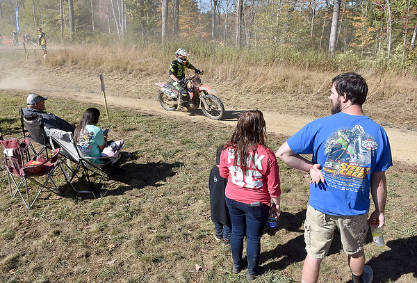 (Brad Davis/The Register-Herald) Riders zoom by fans and family members of riders who sit close to the track as they take in the action during the GNCC racing event Saturday afternoon at the Summit Bechtel Reserve.