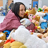 (Brad Davis/The Register-Herald) Shopper Sharissa Hutchinson digs into a mountain of stuffed animals as she searches for the perfect one during the Wyoming County Toy Fund event Sunday morning at Wyoming East High School.