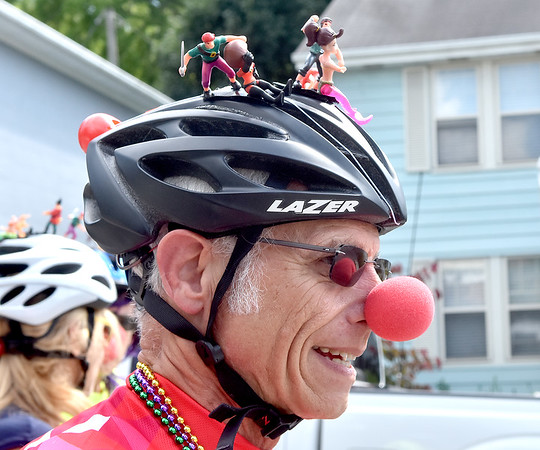 (Brad Davis/The Register-Herald) Bicycle riders roll along with action figures attached to their helmets during a special parade honoring the life of Chally Erb, kicking off a night of memorials Saturday afternoon in Lewisburg. The Mardi Gras-style parade was a moving monument to his life as a veteran, family man, performer and athlete.