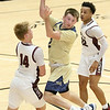 (Brad Davis/The Register-Herald) Shady Spring's Luke LeRose dishes to an open teammate as he drives into the paint between Woodrow Wilson defenders Richard Law, right, and Maddex McMillion Saturday night at the Little General Battle for the Armory.