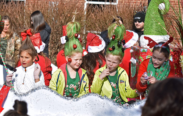 (Brad Davis/The Register-Herald) A young parade participants sport Grinch hairstyle as they toss candy to the masses during the Beckley Christmas Parade Saturday morning.