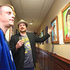 "Matt Mullins and Jason Lockart look at artworks on display, at a ""Vile and Wunderbar"" art show at Sir Walters Tavern Thursday. Mullins organized the event, which includes West Virginia themed art and a silent auction with the proceeds going toward funding the release of his new album ""Partly Pandemonium, Partly Love."" (Jenny Harnish/The Register-Herald)"