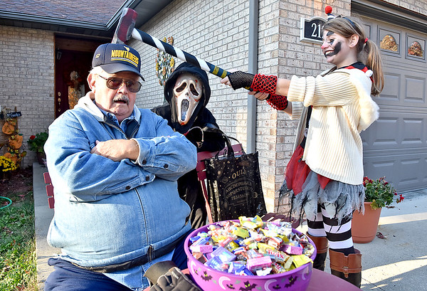 (Brad Davis/The Register-Herald) 12-year-old insane clown Maddigan Clark, right, has a little fun showing off her prop sledgehammer for the camera with grandfather David Goode, who takes the brunt of the pose as her 10-year-old brother Myles, dressed up as the villian from the Scream series, peeks in at middle as the kids prepare to set off for Trick or Treat and David is ready with the candy Saturday evening on Parkwood Drive.