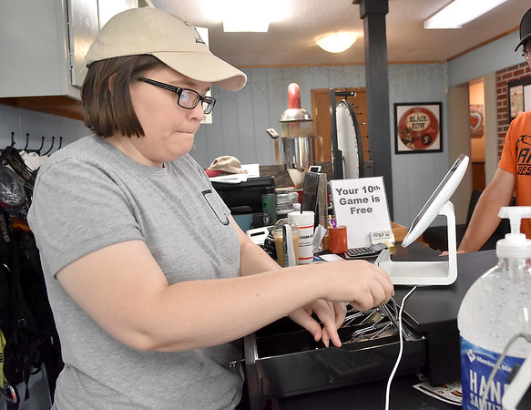 (Brad Davis/The Register-Herald) Chocolate Moose employee Hannah Warden holds down the fort as she handles regular duties around the coffee shop, mini golf and climbing gym while owner Kevin Traube is out of town for a couple days Sunday afternoon.