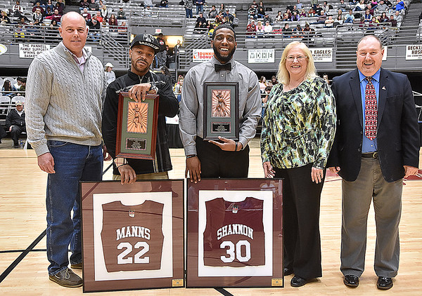(Brad Davis/The Register-Herald) Former Woodrow Wilson basketball players Marcus Manns, left, and Cam Shannon hold their new hardware and framed jerseys after being inducted into the Flying Eagles boys basketball Hall of Fame during a halftime ceremony Friday night at the Beckley-Raleigh County Convention Center. Joining them in the photo are Tim and Myra Harper along with broadcaster Maris Lowery, far right.
