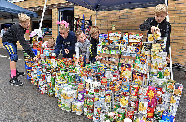 (Brad Davis/The Register-Herald) From left, young players and league members Brodie James, Raelyn McDaniel, Rylee Price, Landrie James, R.J. McDaniel and Chase Price stack and organize hordes of canned food and other items at the conclusion of the Shady Spring Youth Football Athletics' Fall Festival Saturday afternoon at Shady Spring High School. Though rain shortened the outdoor portion of the event, the food drive portion was a massive success, with five teams of players, coaches and cheerleaders each competeing to see who could donate the most items for the Beckley-based non-profit One Voice's food pantry, blessing box and their Food for Angels program, which provides meals and other food for school-aged children in need. Vendors' fees for the event also went to One Voice. The team that raised the least is scheduled to receive pies in the face, tentatively scheduled sometime Tuesday evening at Shady Spring Middle School.