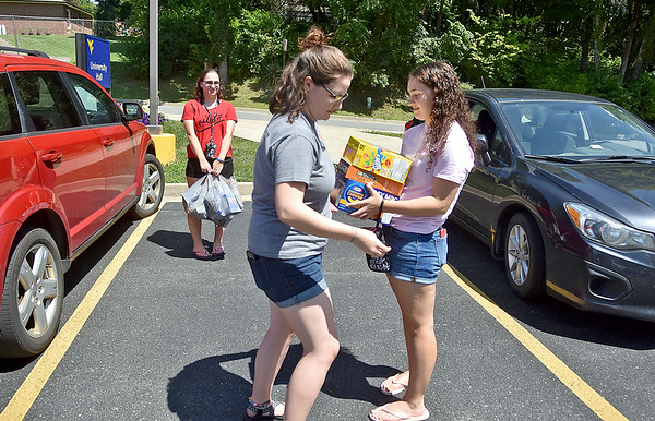 (Brad Davis/The Register-Herald) WVU Tech student and Handley native Jamie Fauver, middle, gets a pair of helping hands from sisters Olivia, left, and Elizabeth in carrying groceries back to her dorm as she and other students get a head start on moving in for the school year Saturday afternoon. Jamie, a nursing major, is entering her senior year at Tech, while the two sisters will be starting their freshman years at Marshall. WVU tech's official move-in day happens today.