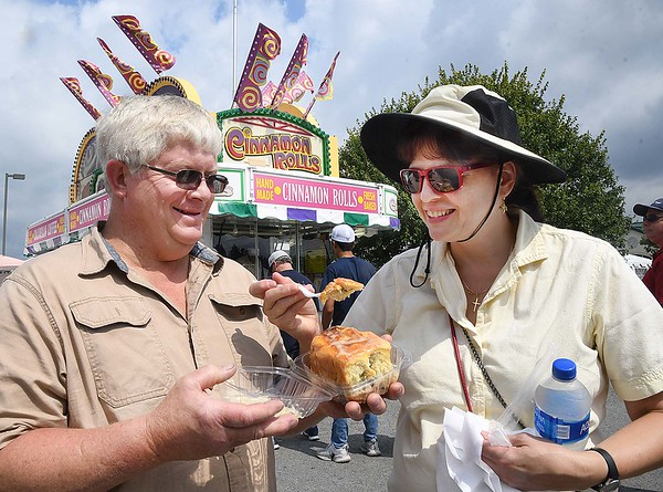 Ralph Smith, left and Kathryn Walker, of Beckley, share a cinnamon  roll at the State Fair in Fairlea Friday afternoon.<br /> (Rick Barbero/The Register-Herald)