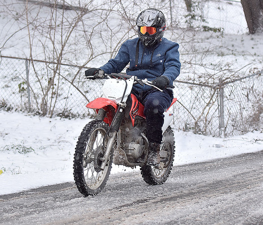 (Brad Davis/The Register-Herald) Beckley resident A'Leeae Martin uses a trusty dirt bike to get around the slushy neighborhood roads as he travels down Kessinger Street on a cold, snowy Sunday afternoon.