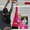 (Brad Davis/The Register-Herald) Liberty's Morgan Marty leaps to hit the ball to her left to avoid Oak Hill defender Marcayla King's hands during the Coalfield Conference Volleyball Tournament Saturday afternoon at Shady Spring High School.