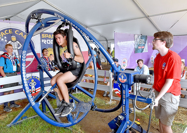 (Brad Davis/The Register-Herald) Spanish scout Eduardo Goni, left, goes for a spin at NASA's Space Camp area during the last day of World Scout Jamboree activities Thursday afternoon at the Summit Bechtel Reserve.