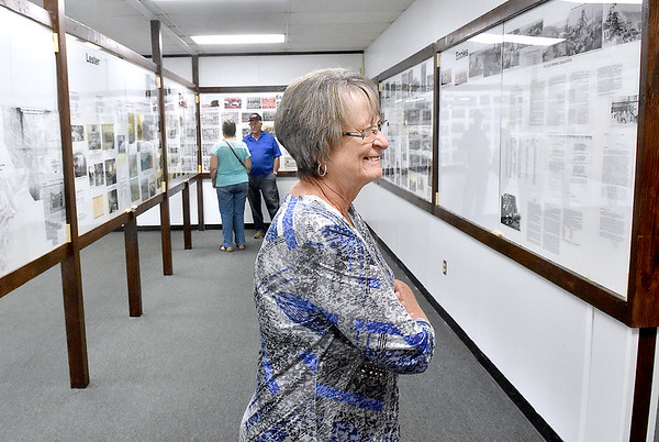 (Brad Davis/The Register-Herald) Lester area natives Lois Trump looks over the displays packed with photos and history of the once booming region inside the newly opened Trap Hill History Museum Friday afternoon inside the former Lester Elementary School, now Lester's City Hall.