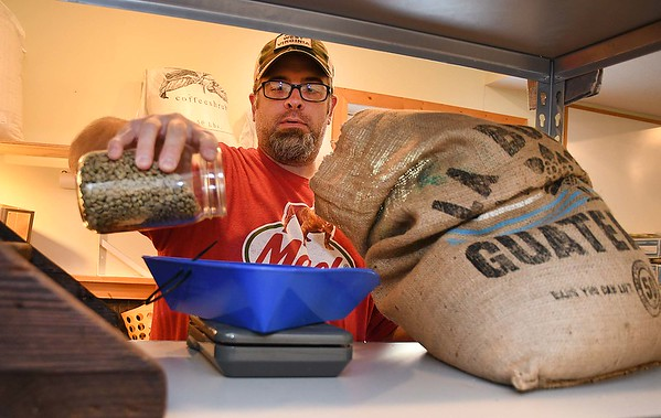 Jason Young, owner, of White Oak Bee Company, measuring coffee grinds for his home-based local coffee roaster business. <br /> (Rick Barbero/The Register-Herald)