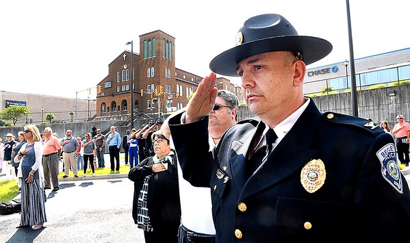 Beckley police chief Lonnie Christian, salutes as his officeres raise the flags during the ribbon cutting dedication ceremony held at the new Beckley Police Department headquarters on 501 Neville Street.<br /> (Rick Barbero/The Register-Herald)