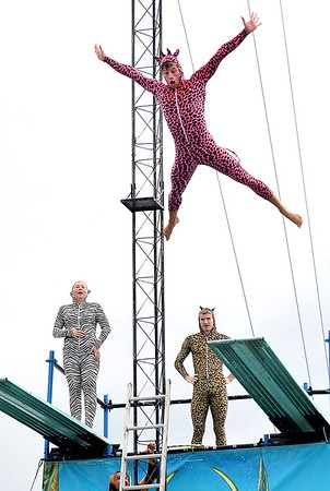 Dylan Glumac-berberich, jumps in his giraffe costume during the High Dive Show at the State Fair in Fairlea Friday afternoon.<br /> (Rick Barbero/The Register-Herald)