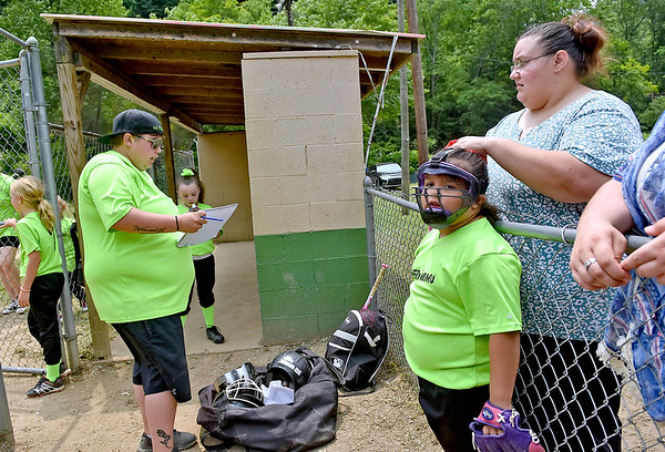 (Brad Davis/The Register-Herald) Crystal McCourt, far right, adjusts five-year-old daughter Lexi's mask as her coach Katelyn Foster, left, draws up the HERricanes lineup prior to their game Staurday afternoon in Pettus.