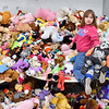 (Brad Davis/The Register-Herald) Young volunteer Danica Lacy, 9, performs the task of climbing onto a giant pile of stuffed animals and dishing them out to shoppers during the Wyoming County Toy Fund event Sunday morning at Wyoming East High School.